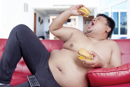 Image of hungry overweight person sitting on the sofa while watching tv and eat two burgers at home